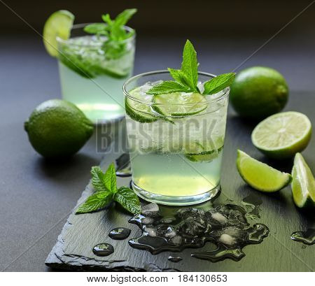 Cold cocktail with lemon liqueur, lime, tonic, ice in two glasses or mojito cocktail on dark background. Close-up.