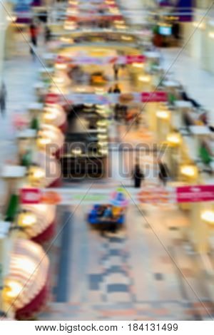 Abstract defocused motion blurred young people walking in the shopping center. Shopping gallery, arcade, top view on two floors, urban lifestyle concept. Vertical background.