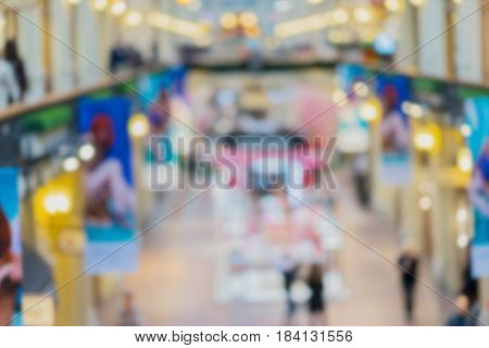 Abstract defocused motion blurred young people walking in the shopping center. Shopping arcade, top view of two floors, Cafe with parasols . Bright colors, background.
