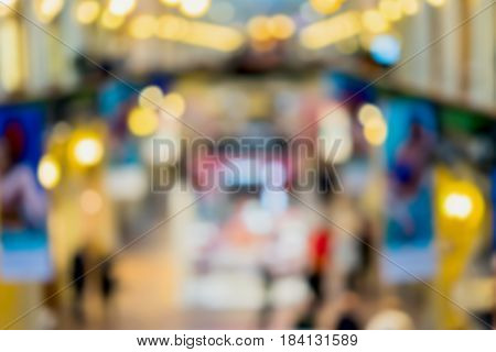 Abstract defocused motion blurred young people walking in the shopping center. Shopping arcade, top view of two floors, Cafe with parasols . Bright colors, urban lifestyle concept, Blurred image background for design