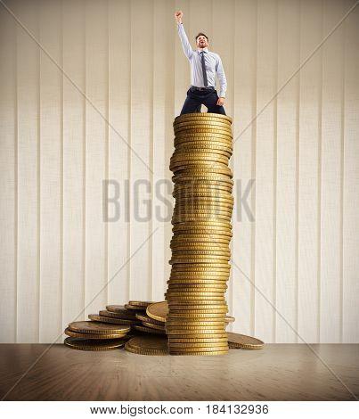 Happy businessman exults over a stack of golden coins