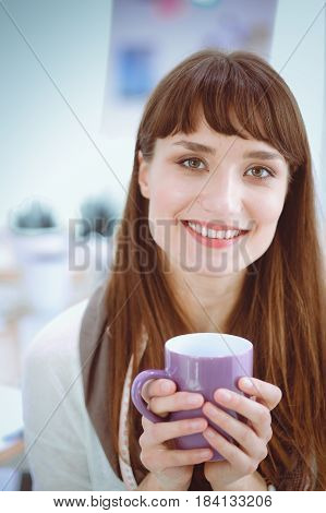 Female fashion designer with cup of coffee.