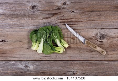 Fresh Chinese Bok Choy and paring knife on rustic wood in flat lay format