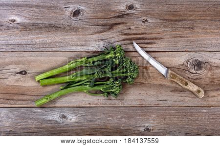 Fresh Chinese broccoli and paring knife on rustic wood in flat lay format