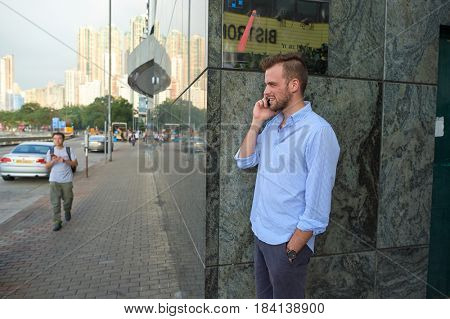 HONG KONG - OCTOBER 25, 2015: handsome man talking on the cellphone in Kennedy Town. Kennedy Town is at the western end of Sai Wan on Hong Kong Island