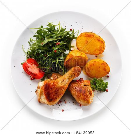 Roast chicken drumsticks with potatoes on white background
