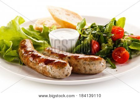 Grilled sausages with vegetables on white background