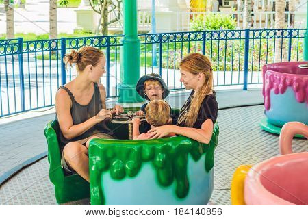 Happy Mothers And Little Sons Riding On A Merry-go-round Carousel Together, Smiling And Having Fun A