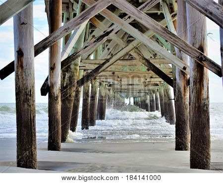 Under the pier sitting in the sand out of the summer heat.