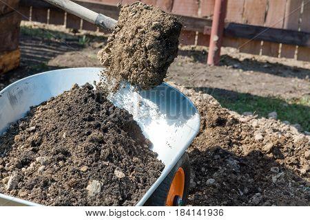 Garden wheelbarrow with the earth. To fill the earth in a wheelbarrow for construction.