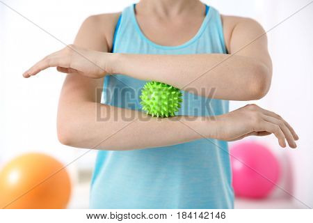 Woman doing exercises with rubber ball in clinic, closeup