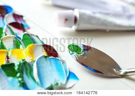 Colorful paints, palette knife and used tube, closeup