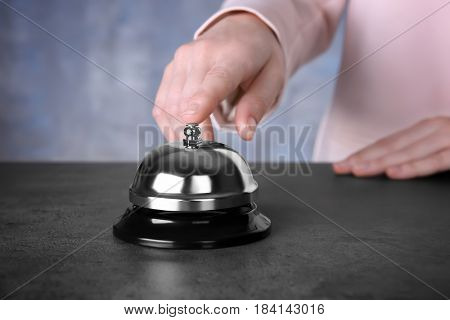 Businesswoman ringing service bell in hotel lobby