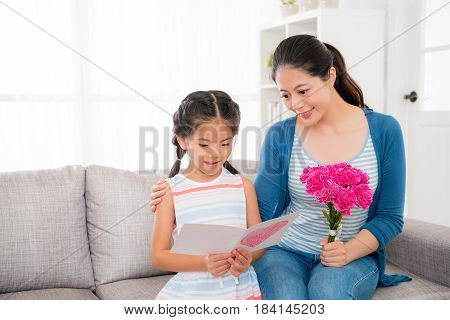 Mother And Daughter Sitting On Sofa In Living Room