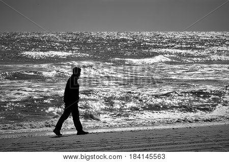 Man walks along the coast as night falls.