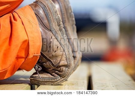 Close up of a pair of brown leather shoes with toes bent and heel facing up and the hem of a pair of orange coveralls kneeling on a wood board