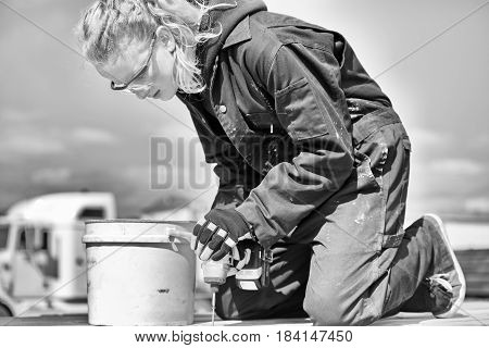 A black and white picture of teenage girl with long hair in a ponytail wearing safety glasses and coveralls drilling a screw into a piece of wood outdoors