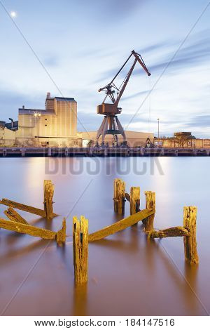 View at evening of the Nervion river near the city of Bilbao Basque Country Spain. Industrial port area with crane and factory in the district of Zorroza.