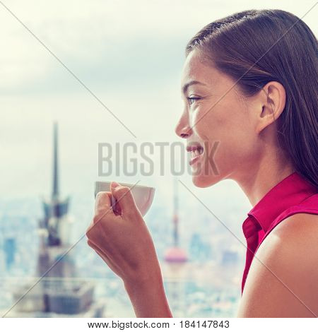 Asian woman enjoying afternoon high tea in luxury cafe or high end restaurant with city view of Shanghai's skyline. Chinese businesswoman lady drinking hot cup of coffee relaxing.