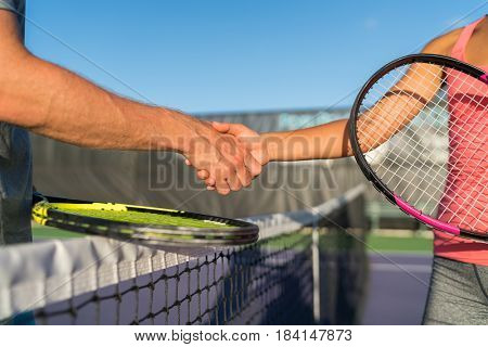 Tennis players shaking hands at court net at end of fun game. Man and woman playing recreational tennis handshaking with tennis racquets.