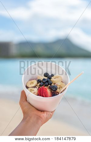 Acai bowl food closeup of healthy breakfast take-out on ocean background at hawaii beach. Berries and fresh fruits outdoors for a weight loss diet. Eating local Hawaiian dish.
