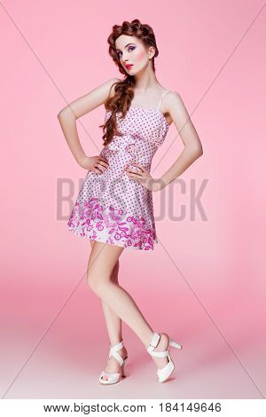 Beautiful young woman with long red braided hair and bright colourful makeup wearing dress standing on pink background. Pin up style. Copy space.
