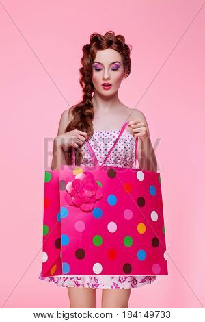 Beautiful red head young woman with bright make-up in flirty dress holding colorful shopping paper bag over pink background. Girl looking inside bag. Copy space.