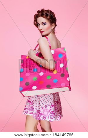 Beautiful red head young woman with bright make-up in flirty dress holding colorful shopping paper bag over pink background. Copy space.