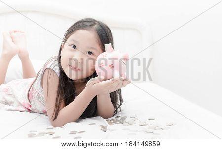 Cute Girl Show Piggybank On Bed