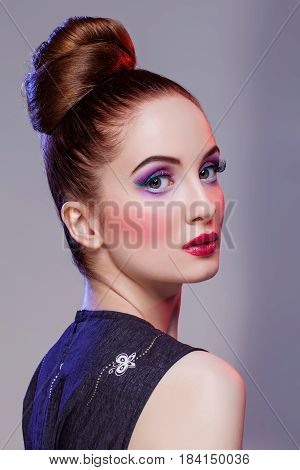 Beautiful young woman with hairdo and bright purple tone make-up. Doll style. Beauty shot on grey background. Copy space.