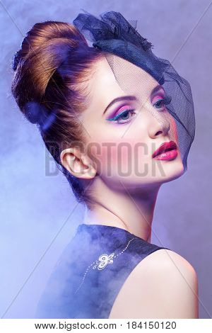 Beautiful young woman in small black veil hat cap with hairdo and bright purple tone make-up. Doll style. Beauty shot on grey smoky background. Copy space.