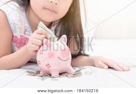 Girl Hand Put Money To Piggybank On Bedroom