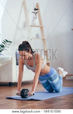 brunette woman with do abdominal exercises with wheel. Workout exercise at home to lose weight