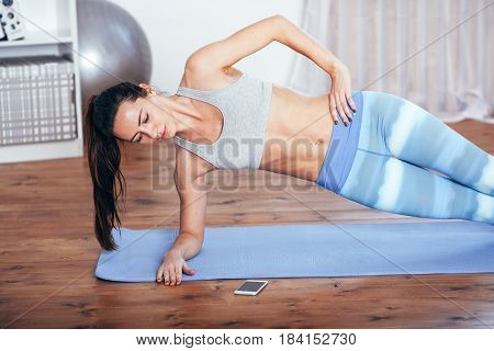 Slim fitness young brunette woman Athlete girl doing side plank exercise at home and using smarthpone