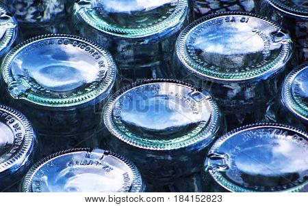 Abstract composition of glass bottles placed upside down and shoing the sky by reflection
