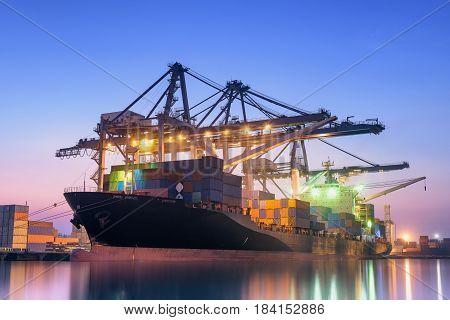 Cargo ship unloading container at twilight., Cargo ship terminal.