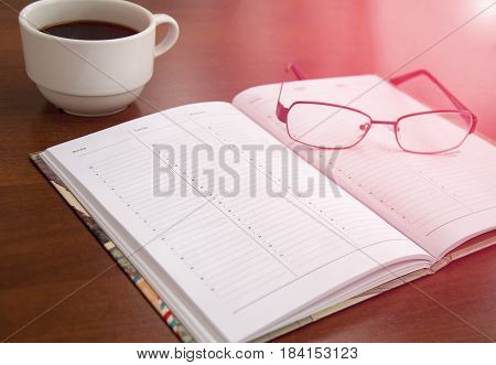 blank checklist on wooden table With coffee and glasses