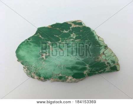 A flat green malachite slice cut from a larger rock