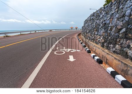 Beautiful bicycle road sign in the curve road near the ocean at Nern Nang Phaya viewpoint. Chanthaburi ProvinceThailand