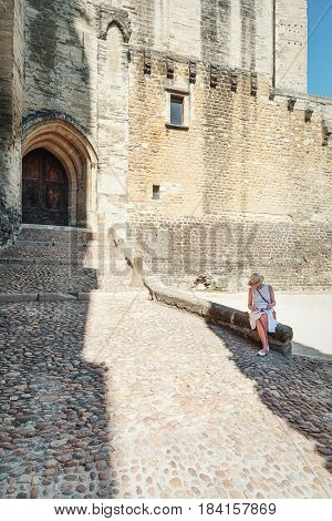 Avignon, France, September 9, 2016: Older woman on a stone wall reads a book for a church in Avignon.