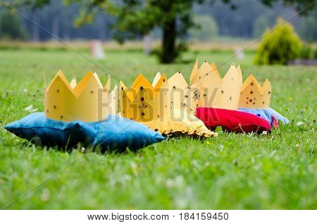 In the green meadow on the colored pads shunted stylized princess crowns.