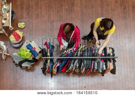 Two women in the shop chooses colored clothes from traders offer.