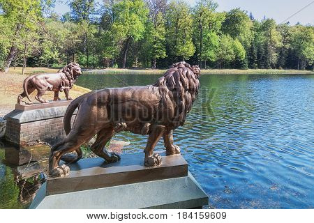 Two lion statues guard the pond in Het Loo Park ocated in Apeldoorn in the Netherlands
