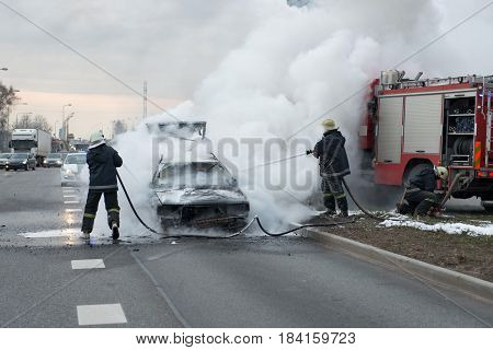 A few minutes in the street burnt car. Traffic is stopped. Firefighters eliminate fire.