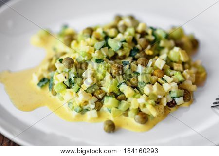 Traditional russian mayonnaise salad with eggs on white plate