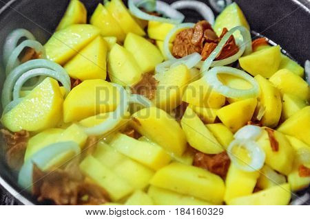 Potato with mushrooms and onion on frying pan