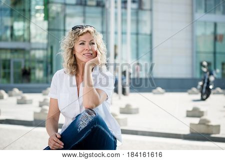 Senior woman thinking something, sitting with legs crossed