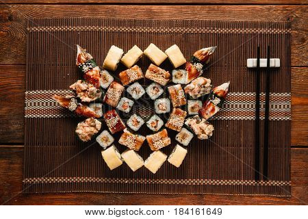 Japanese assorted tasty fresh sushi set served on brown straw mat, flat lay. Food art, mosaic of delicious colorful rolls. Luxury restaurant menu photo.