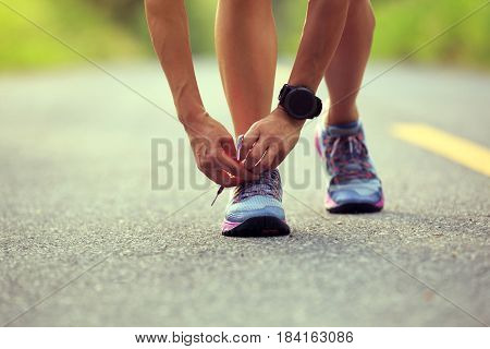 young fitness woman runner tying shoelace before run on forest trail