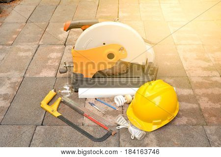 The tools supplies cutting tool chisel and helmet put on brick under the sunlight